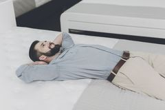 Een mens kiest een matras voor zich in de opslag Hij ligt op één van hen Stock Afbeelding