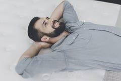 Een mens kiest een matras voor zich in de opslag Hij ligt op één van hen Stock Foto