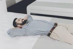 Een mens kiest een matras voor zich in de opslag Hij ligt op één van hen Royalty-vrije Stock Fotografie