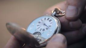 Een mens kijkt op het tijdstip van oude zakhorloges en sluit hen Sluit omhoog stock video