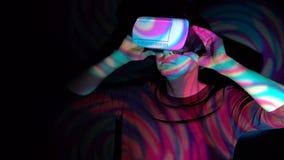 Een mens kijkt virtuele werkelijkheid gebruikend een VR-Helm in de schijnwerper stock video