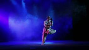 Een mens in kimono is bezig geweest met karate - voert oefeningen tegen een achtergrond van gekleurde rook uit stock video