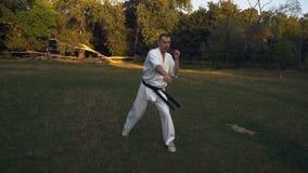 Een mens in Kimono, Karatevakman, de Strijd van de Loodschaduw, maakt een Reeks Stakingen met Voeten en Handen, Treinen in stock videobeelden