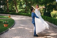 Een mens in een klassiek kostuum draait zijn bruid de kerel hief het meisje in zijn wapens op en liefdes die haar bekijken, hief  royalty-vrije stock foto's