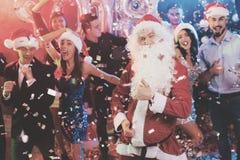 Een mens kleedde zich aangezien Santa Claus pret bij een Nieuwjaarpartij heeft Samen met hem hebben pretvrienden Stock Fotografie