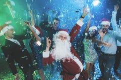 Een mens kleedde zich aangezien Santa Claus pret bij een Nieuwjaarpartij heeft Samen met hem hebben pretvrienden Stock Foto's
