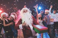 Een mens kleedde zich aangezien Santa Claus pret bij een Nieuwjaarpartij heeft Samen met hem hebben pretvrienden Royalty-vrije Stock Foto