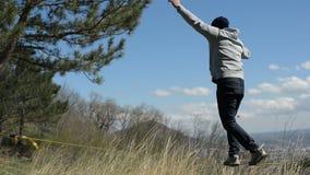 Een mens kleedde zich in een hoed en een baard, tribunes tot gang in de wind tegen de achtergrond van de bergen van de Kaukasus v stock videobeelden