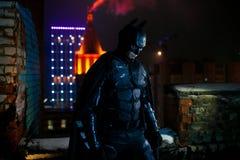 Een mens kleedde zich in masker, pantser en manteltribunes tegen de achtergrond van de lichten van de nachtstad royalty-vrije stock foto's