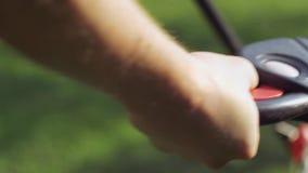 Een mens klikt op een knoop van begingrasmaaimachine stock videobeelden