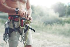 Een mens knoopt een knoop op een het beklimmen uitrusting royalty-vrije stock afbeelding