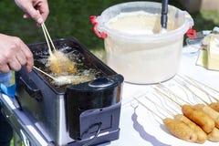 Een mens kookt gefrituurde worstbroodjes stock foto's