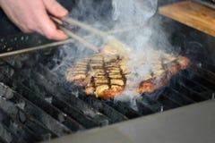 Een mens kookt een lapje vlees op de grill heel wat rook stock foto