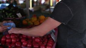 Een mens koopt groenten bij een markt de dag