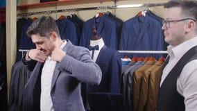Een mens koopt een kostuum in een opslag stock footage