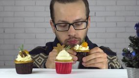 Een mens koos een cupcake en eet greedily stock footage