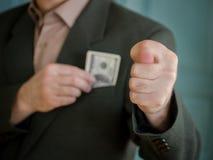 Een mens in een kostuum met één hand verbergt het contante geld in zijn jasjezak, het andere vooruit uitgerekte wapen en toont Fi Stock Afbeeldingen