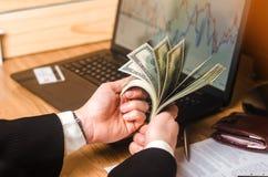 Een mens in een kostuum telt het geld op laptop met economische grafieken Investeringen in onroerende goederen Bedrijfsideeën, su royalty-vrije stock fotografie