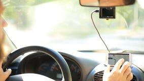Een mens krijgt in de auto en zet de navigator op smartphone aan stock videobeelden