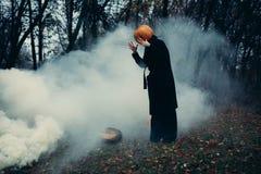 Een mens in een lange zwarte laag met een pompoen in plaats van een hoofd in een vreselijke nachtbos, een vocht en een mist royalty-vrije stock foto