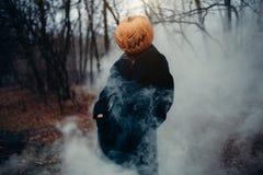 Een mens in een lange zwarte laag met een pompoen in plaats van een hoofd in een vreselijke nachtbos, een vocht en een mist royalty-vrije stock afbeeldingen