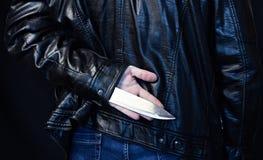 Een mens in een leerjasje houdt een mes achter zijn rug, een zwart gevaar als achtergrond royalty-vrije stock fotografie