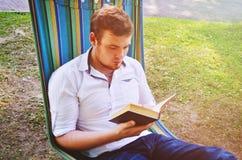 Een mens leest een boek in een hangmat Stock Foto
