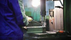 Een mens leidt het boorwerk aangaande metaaldelen Giet vloeistof in het materiaal stock videobeelden