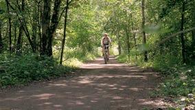 Een mens leidt in het park op Hij berijdt een fiets op een de zomerdag, op speciale sporen stock video