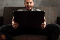Een mens let op een volwassen video op laptop terwijl het zitten op de laag Het concept pornografie, de behoeften van mensen, per stock afbeelding
