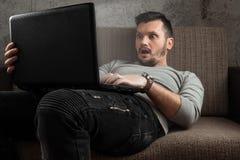Een mens let op een volwassen video op laptop terwijl het zitten op de laag Het concept pornografie, masturbatie, mannelijke beho royalty-vrije stock afbeelding
