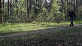 Een mens loopt door het hout die een drank drinken en een plastic fles, draagstoel weggooien stock videobeelden