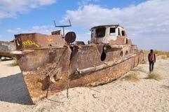 Een mens loopt naast het schipmidden van een woestijn Stock Fotografie