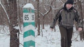 Een mens loopt naast een kwartpost in de de winter bosinspectie van bosbouw stock footage
