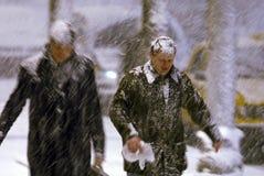 Een mens loopt onder een zware sneeuw stock afbeeldingen