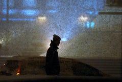 Een mens loopt onder een zware sneeuw stock foto