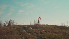 Een mens loopt op een berg met een Canadese vlag in zijn hand De vlag van Canada ontwikkelt zich in de wind stock footage