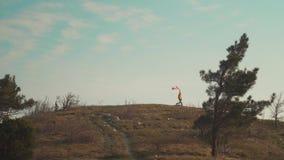 Een mens loopt op een berg met een Canadese vlag in zijn hand De vlag van Canada ontwikkelt zich in de wind stock videobeelden