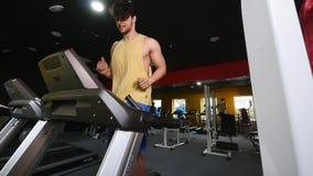 Een mens loopt op een lopende machine in de gymnastiek langzame motie stock video