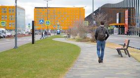 Een mens loopt op een weg in de stad stock video