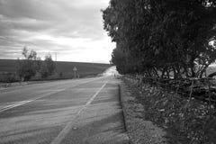Een mens loopt op een lege weg Stock Fotografie