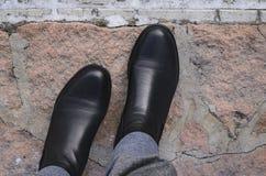 Een mens loopt in zwarte leerlaarzen aan de steenstoep royalty-vrije stock fotografie