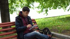Een mens luistert aan muziek en het gebruiken van een tablet in het park stock videobeelden