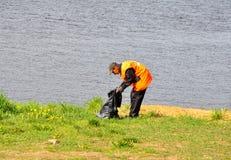 Een mens maakt de rivierbank schoon Stock Afbeeldingen