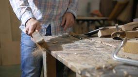 Een mens maakt houten spaanders met een borstel schoon stock videobeelden