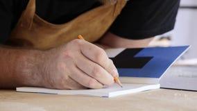 Een mens maakt ingangen in de agenda De mens, een beroeps maakt nota's in een notitieboekje Een timmerman maakt berekeningen in v stock video