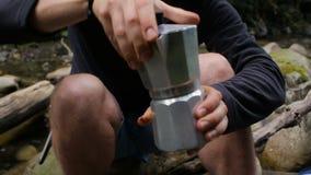 Een mens maakt koffie in een koffiezetapparaat in een kampeerterrein op de rivierbank stock videobeelden
