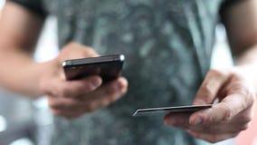 Een mens maakt online aankopen gebruikend zijn telefoon en stelt de te geven creditcard voor Online bankwezen met slimme telefoon stock videobeelden
