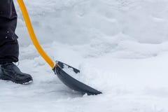 Een mens maakt sneeuw in de yard met een schop na een zware sneeuwval schoon stock afbeeldingen