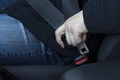 Een mens maakt zijn veiligheidsgordel, close-up vast stock afbeeldingen